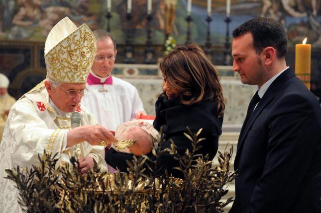 Papa Benedicto XVI bautizando a un niño, en la imagen aparecen también los padres del niño