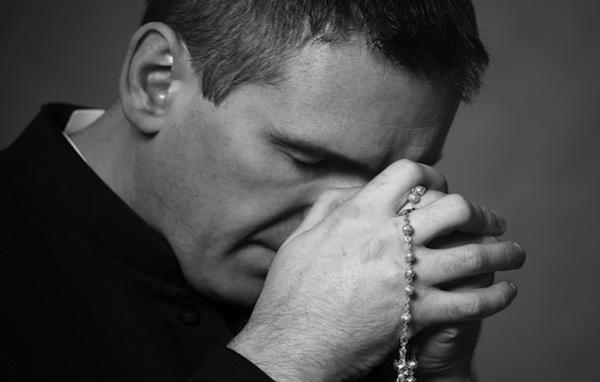 Sacerdote rezando, con el santo rosario en las manos