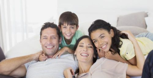 Family smiling together on sofa in living room